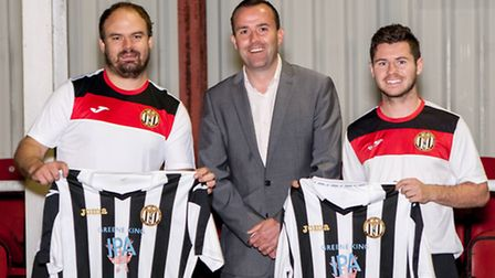 Greene King area manager James Ramm presenting the new Swaffham first team kit to team captain Mike
