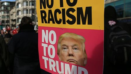 A protestor holds a placard referencing Donald Trump during a demonstration, United for Education, s