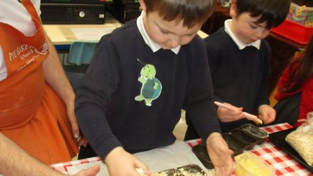 Grimbsy helping the children bake bread. Picture: courtesy of Nelson Infant School
