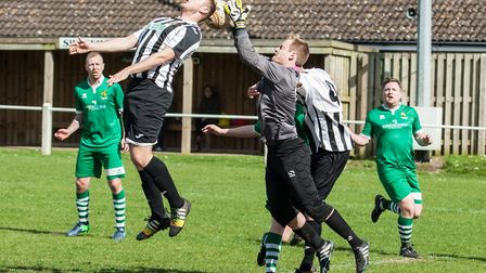 Swaffham Reserves' Robson Pack in an aerial challenge with the keeper.