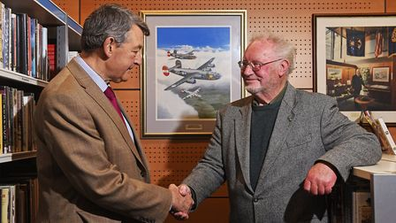 Artist Mike Bailey, right, with his painting which is now in the 2nd Air Division Memorial Library a
