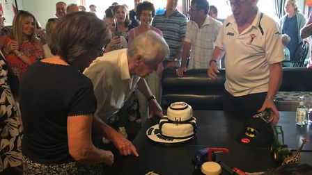 Albert Hudson blows out the candles on his cake with friends and family looking on at Swaffham Town