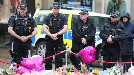 Armed police observing a minute's silence in St Ann's Square, Manchester, in honour of the London Br