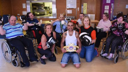 Norfolk amateur boxer, Zaiphan Morris, with residents at John Grooms Court for adults with physical