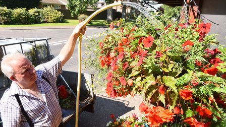 Adrian Thompson, chairman of Filby in Bloom making sure the hanging baskets in the village have a go
