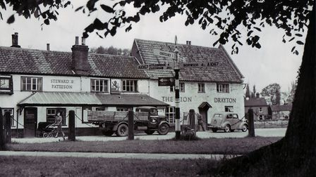 The Village Green with a truck and car in front of The Red Lion. Note: the sign for the train statio