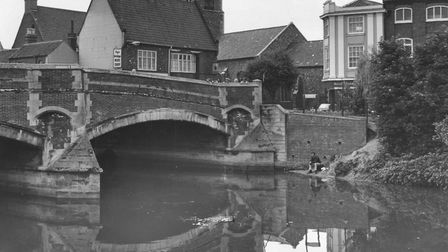 A solitary angler fishes the placid waters of the Wensum at Fye Bridge in Norwich in July, 1965. Pic