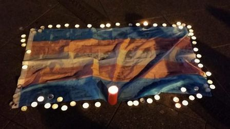 Trans flag with candles during a vigil at UEA (Photo: Katy Jon Went)