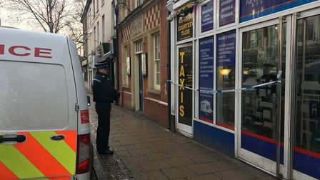 A PCSO standing outside the Courtesy Taxis base on Prince of Wales Road in Norwich after an early mo