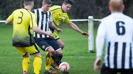 Joe Jackson in the thick of the action for Swaffham Town during their 6-1 win over Wisbech St Mary i