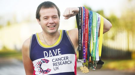 IT technician Dave Walton with the medals he has won from running a half marathon every month this y
