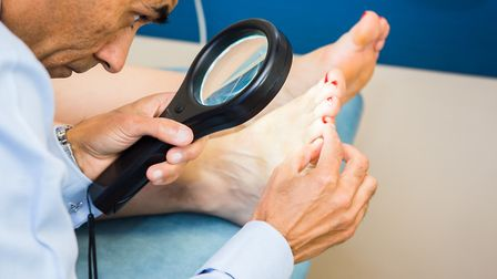 Dr Deepak Rallan uses a magnifier to spot early signs of skin cancer on the surface of the skin.