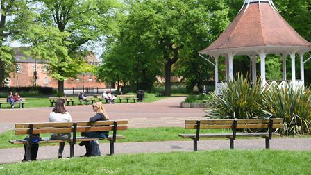 People chat in the sunshine by the bandstand in Chapelfield Gardens. Picture: DENISE BRADLEY