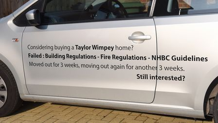 Justin and Tracy Revell's car advertising the problems they have had with their new build home Pictu