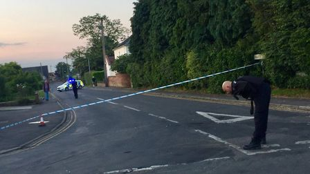 A police officer examines the scene of an RTC in Hethersett, where the junction of Henstead Road and