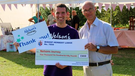 Simon Wright (left), chief executive officer of Nelson's Journey, receiving a donation of £5,650 fro