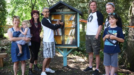 Jimmy Mavroudis cuts the ribbon to open the resident's new mini library book swap station at the Old