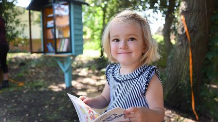 Georgia Murray, four, reads a book from the new mini library book swap station at the Old Library Wo