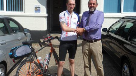 Nathan Cunning handing over the £700 sponsor money to Paul Ray, MS Therapy Centre manager.