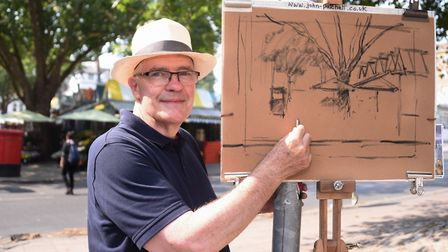 Artist John Patchett at work on a pastel drawing of Norwich Market for Norfolk Day. Picture: DENISE