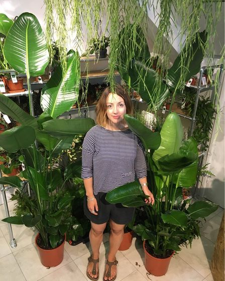 Part owner Michelle stands among the giant Bird of Paradise plants. Picture: Michael Popp