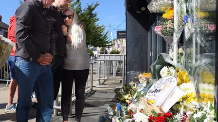 Dawn Peri, right, with close family and friends, takes comfort from the messages and floral tributes