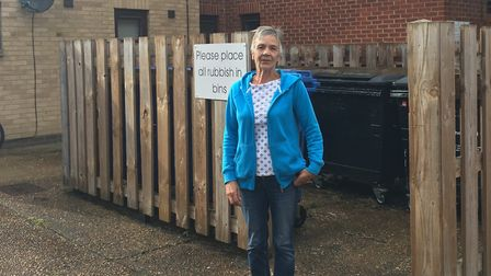 Valerie Roberts standing next to bins which residents feel are contributing to a rat problem on the