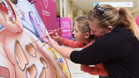 Arabella Ward, five, and her mum, Hayley, have a go at removing organs from a large version of Opera