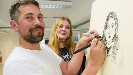 Artist Tom Hill who sketches using both hands, working on a portrait at NUA, with his subject, Annab