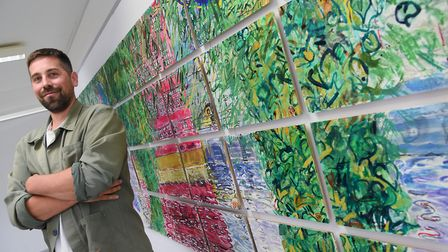Artist Tom Hill who sketches using both hands, with Landscape in 36 pieces, part of his work on disp