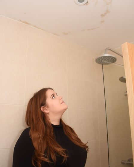 Abigail Nicholson looks at the stains where water had been pouring through the light fitting in the