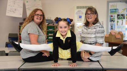 Megan Baxter, eight, demonstrates her gymnastic skills in class to head teacher Gayle Long, right, a