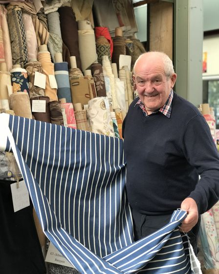 Barry Read, retired owner of Barry Read's Fabrics on the market, holding fabric