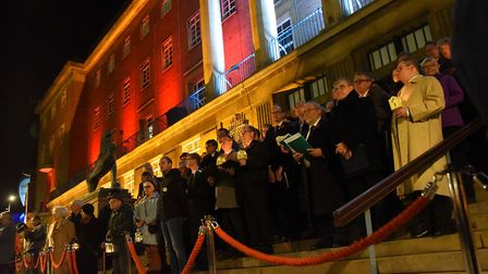 The dignitaries and choir at City Hall, lit up in red, white and blue, for the Vigil of Peace for Ar