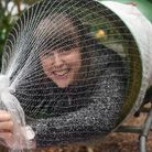 Chloe Tucker is wrapped up for Christmas as she goes through the Christmas tree netting machine at T