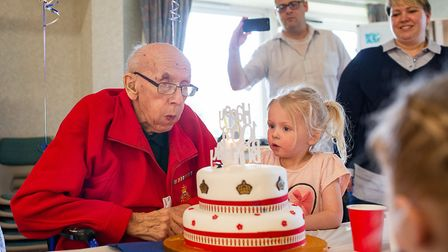 Leonard Boxall blows out the candle on his cake assisted by one of his great-grandchildren on his 10