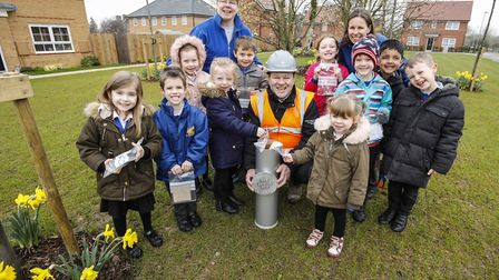 Pupils and staff from Watton Infant and Nursery School burying their time capsule at Knights Park wi