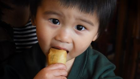 Lucas Ngai, aged two, tries the spring rolls at his family's Baby Buddha Chinese Teahouse. Picture:
