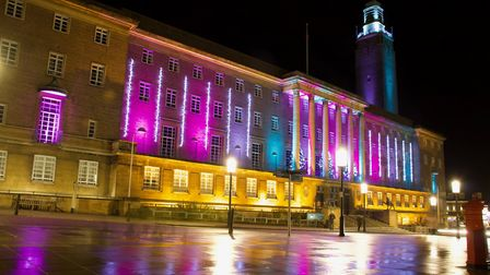 The lights on the City Hall are reflected in the wet pavements.