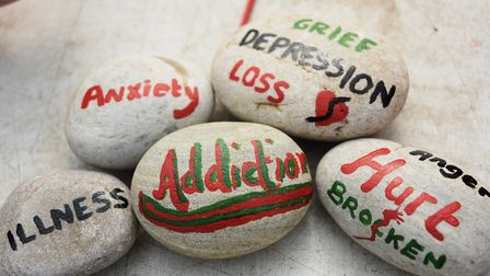 Words on pebbles painted by participants in the Escape Project that sum up everyday pressures that f