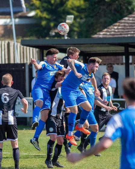 Swaffham Town's Danny Tindall rises above the rest, Wanderers defending en mass.