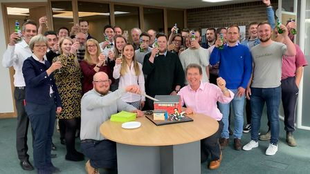 Tim Walsingham and Tony Abel, front, cut the cake with colleagues from Abel Homes. Picture: Abel Hom