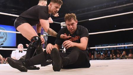 Three 'baddie' wrestlers attack Grant Holt in and out of the ring during his wrestling match at Epic