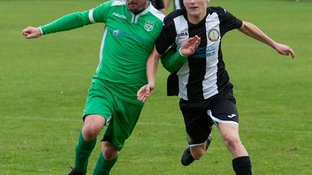Scott Moore shoulder to shoulder with an opponent during Swaffham Town Reserves' 2-1 defeat at the h