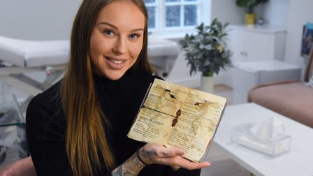Danielle Sheehan, owner of Mae Cosmetics, with the old menu from the Cloverleaf Café found in the fl
