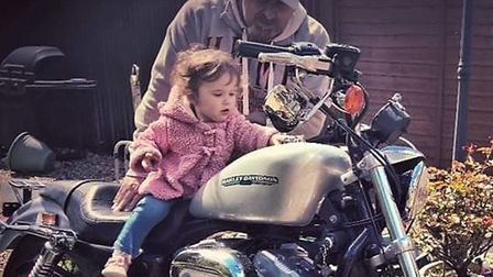 Mark Page with his bike, dubbed the mistress by his wife, and granddaughter Alila. Picture: Steven G