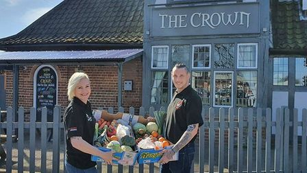 Trina Lake and Bradley Richards with their fruit and vegetable boxes outside The Crown pub in Costes