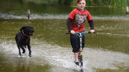 Nine-year-old Jake Barnes gets some speed up as he scooters in the river in Earlham Park in Norwich,