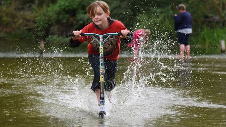 Nine-year-old Jake Barnes gets some speed up as he scooters in the river in Earlham Park in Norwich