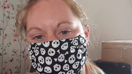Volunteer Rose with a mask produced by the group. Picture: Submitted by Libby Double